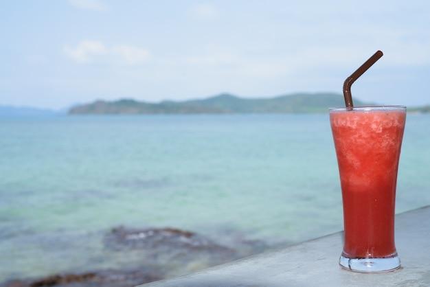 Erfrischender wassermelonen-smoothie mit blick auf den strand