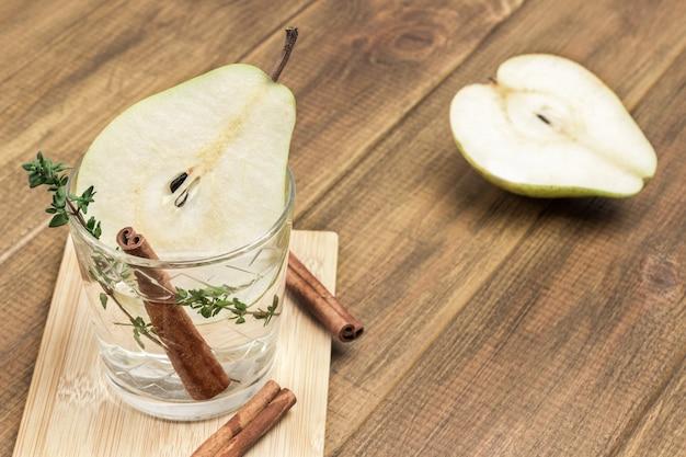Erfrischendes birnengetränk, zimtstange und thymianzweig im glas. birnenscheibe auf dem tisch. draufsicht