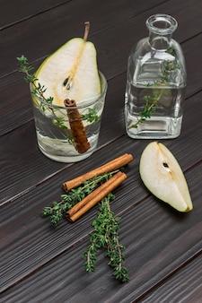 Erfrischendes birnengetränk, zimtstange und thymianzweig im glas. birnenscheibe auf dem tisch. flasche mit wasser und thymianzweig.