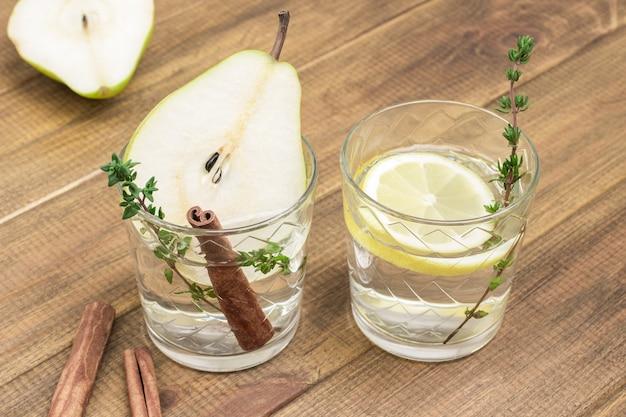 Erfrischendes birnengetränk, zimtstange und thymianzweig im glas. glas mit zitrone und thymianzweig. birnenscheibe und zimtstangen auf dem tisch. draufsicht