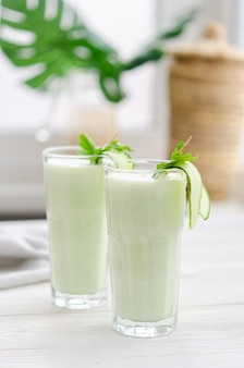Erfrischendes fermentiertes milchgetränk mit gurke und kräutern. zwei mit so einem cocktail in einem hellen interieur auf einem weißen tisch.
