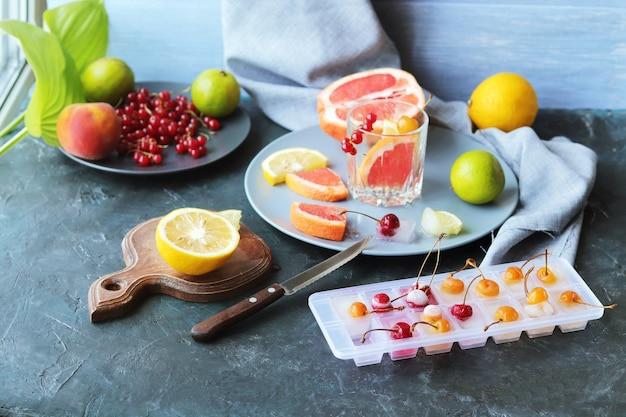 Erfrischendes getränk aus zitrusfrüchten, beeren, minzblättern und eis auf dem tisch, hausgemachte cocktails