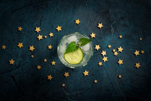 Erfrischendes getränk mit eis, gurke und minze auf einem dunkelblauen hintergrund mit sternen. konzept nachtclub, nachtleben, party, durst. flache lage, draufsicht