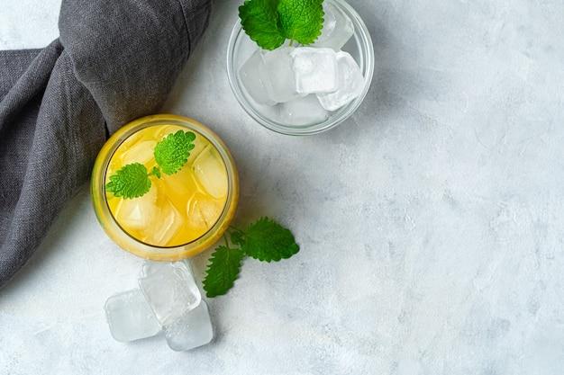 Erfrischendes getränk, orangencocktail mit eis und minze auf einem grauen schreibtisch. draufsicht mit kopierraum.