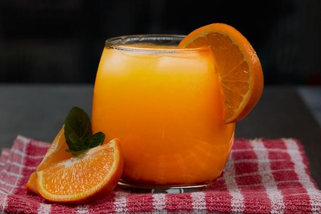 Erfrischendes glas mit frischem orangensaft, eis und orangen auf einem holztisch im dunklen hintergrund