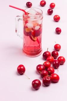 Erfrischendes sommerapfelgetränk mit eis im glas. kleine rote äpfel auf weißem hintergrund. draufsicht.