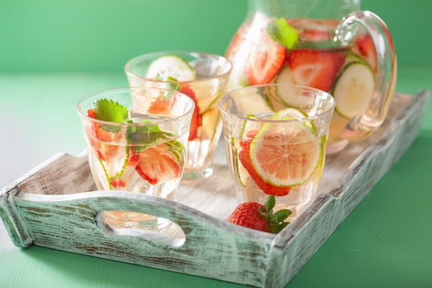 Erfrischendes sommergetränk mit erdbeer-gurken-limette in glas und gläsern