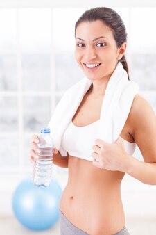 Erfrischt werden. schöne junge frau in sportkleidung, die eine flasche mit wasser hält und in die kamera lächelt