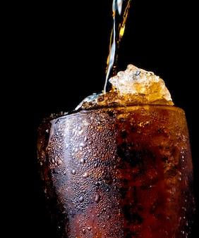 Erfrischungsgetränk, das auf glas mit eis gegossen wird, das auf dunklem hintergrund mit beschneidungspfad und kopienraum isoliert wird. auf der transparenten glasoberfläche befindet sich ein wassertropfen.