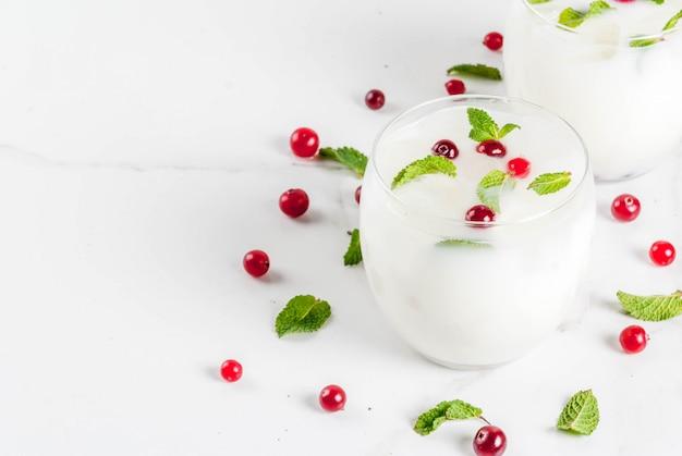 Erfrischungsgetränk der herbst- und winterzeit mojito-cocktail der weißen weihnacht mit moosbeere und minze auf weißer tabelle