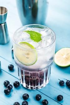 Erfrischungsgetränke im sommer, blaubeerlimonade oder mojito-cocktail mit zitrone, frischen blaubeeren und minze,
