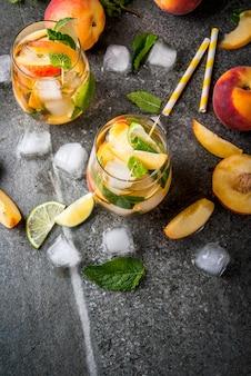 Erfrischungsgetränke im sommer. pfirsich mojito mit limette, pfirsich und minze. mit den zutaten auf einem dunklen steintisch. ansicht von oben