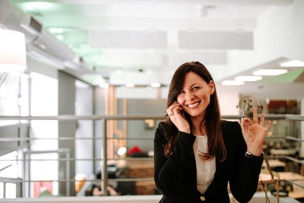 Erfüllte geschäftsfrau, die auf dem smartphone und dem gestikulieren spricht.