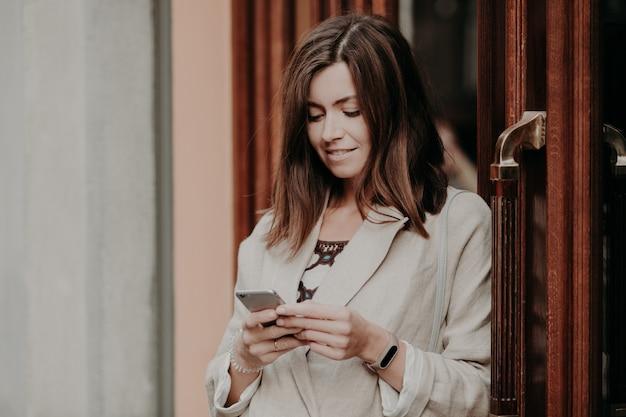 Erfüllte geschäftsfrau hält den modernen handy an, gekleidet in der weißen jacke