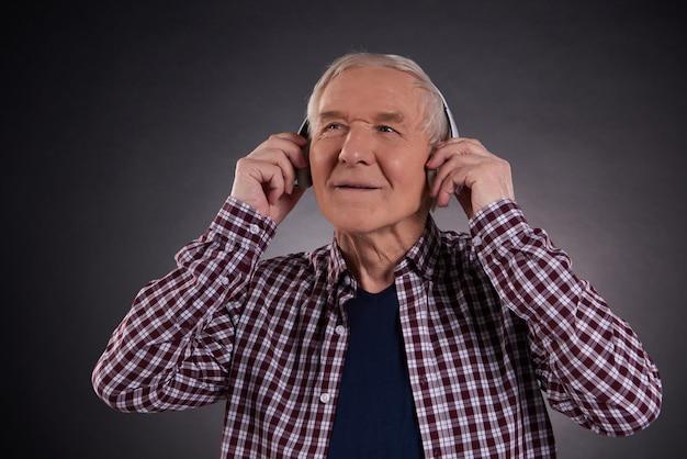 Erfüllter alter mann, der musik hört.