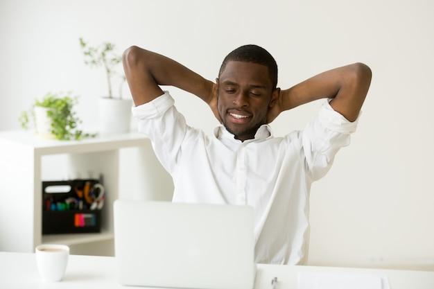 Erfüllter glücklicher afroamerikanermann, der mit kaffee und laptop sich entspannt