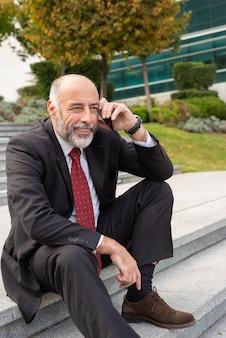 Erfüllter glücklicher grauer behaarter wirtschaftsführer, der am telefon spricht