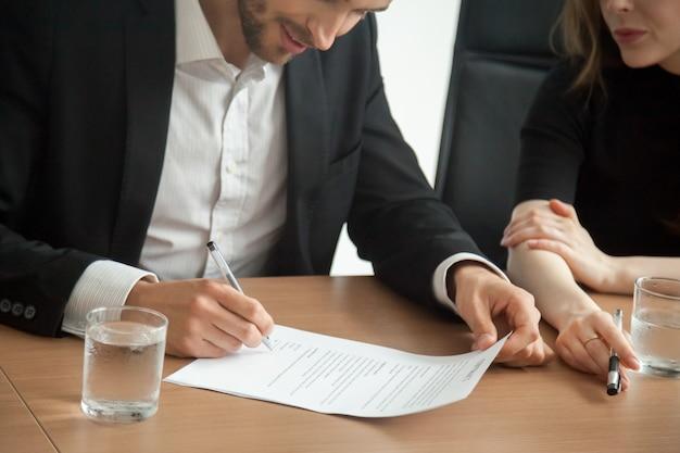 Erfüllter lächelnder geschäftsmann in unterzeichnendem vertrag der klage am sitzungskonzept