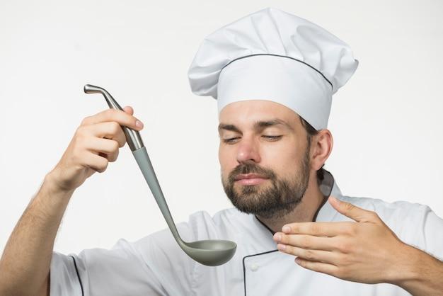 Erfüllter männlicher chef, der schöpflöffel hält, genießt den geruch einer suppe