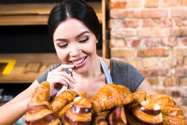Erfüllter weiblicher bäcker, der frisch gebackenes hörnchen betrachtet