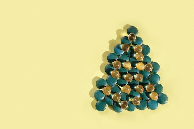 Ergänzungen und vitamine in form von weihnachtsbaum auf gelbem hintergrund, kopienraum.