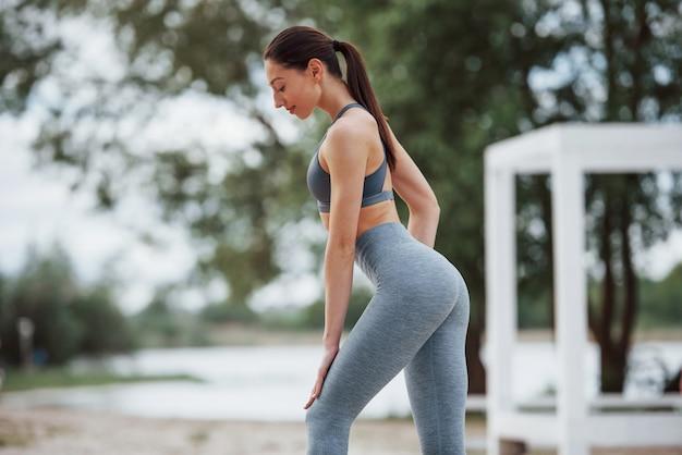Ergebnisse der ernährung und des trainings. brünette mit schöner körperform in sportlicher kleidung haben fitness-tag am strand