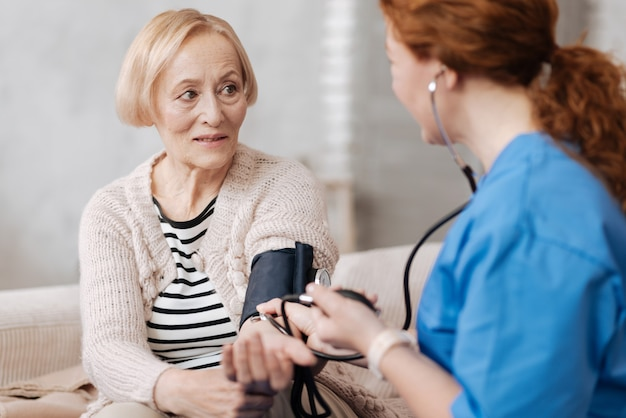 Ergebnisse für die diagnose. schöne, professionell ausgebildete frau, die spezielle ausrüstung einsetzt, während sie während des regelmäßigen besuchs eine untersuchung des gesundheitszustands des patienten durchführt
