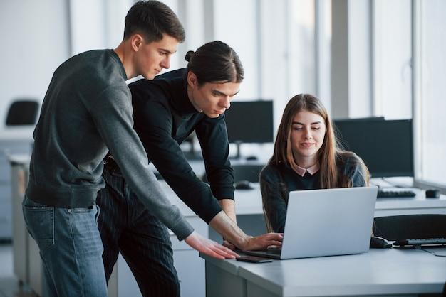 Ergebnisse werden es wert sein. gruppe junger leute in freizeitkleidung, die im modernen büro arbeiten