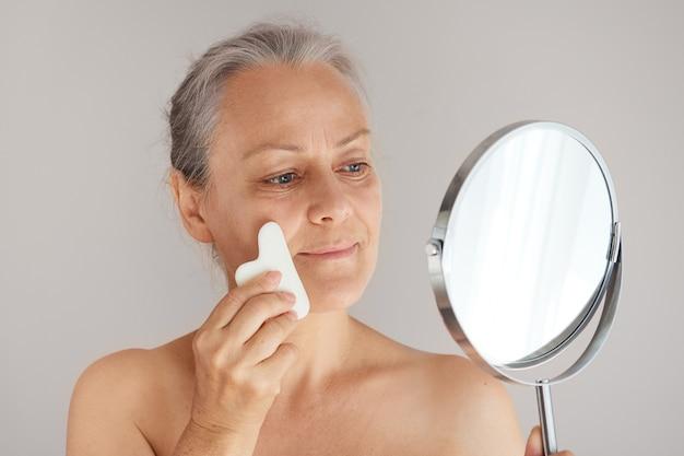Ergraute reife frau, die ihr gesicht mit einem jadebrett massiert, während sie in den spiegel schaut