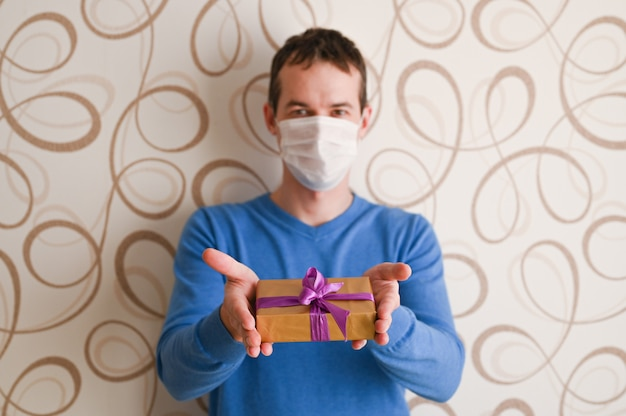 Erhalten sie geschenke, wenn sie krank sind. mann in einer medizinischen maske krankheit und geschenke. coronavirus-konzept.