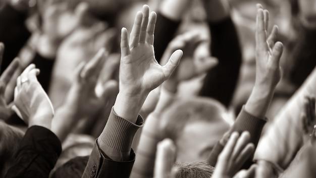 Erhob eine menschliche hand bei der veranstaltung. soziale herausforderungen und abstimmungen