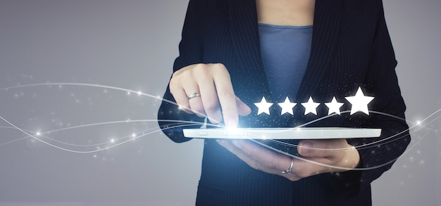 Erhöhen sie das bewertungs- und klassifizierungskonzept. weiße tablette in der hand der geschäftsfrau mit digitalem hologramm fünf sterne 5 bewertungszeichen auf grau. konzept der kundenerfahrung, beste exzellente dienstleistungen.