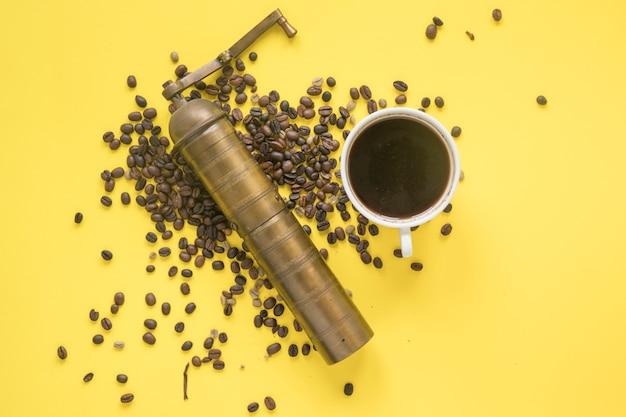 Erhöhte ansicht der alten kaffeemühle und der kaffeebohnen mit heißem kaffee auf farbigem hintergrund