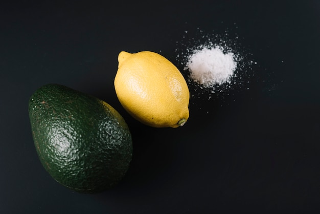 Erhöhte ansicht der avocado; zitrone und salz auf schwarzem hintergrund