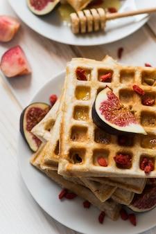 Erhöhte ansicht der belgischen waffeln; honig mit feigenfrucht in der platte