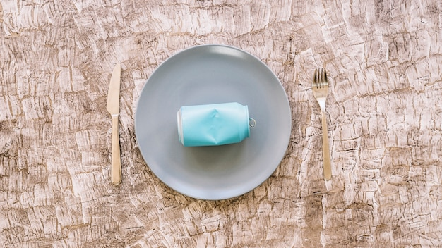 Erhöhte ansicht der blechdose auf platte zwischen küchenmesser und gabel