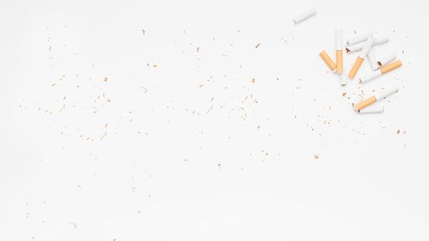 Erhöhte ansicht der defekten zigarette und des tabaks über weißer oberfläche