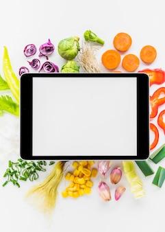 Erhöhte ansicht der digitalen tablette auf frischem gesundem gemüse