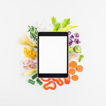 Erhöhte ansicht der digitalen tablette auf verschiedenem gemüse über weißem hintergrund