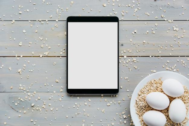 Erhöhte ansicht der digitalen tablette mit eiern und hafern auf platte