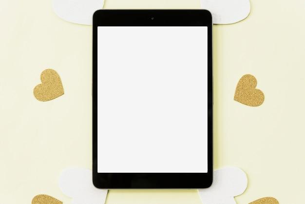 Erhöhte ansicht der digitalen tablette umgeben mit herzaufkleber auf gelbem hintergrund