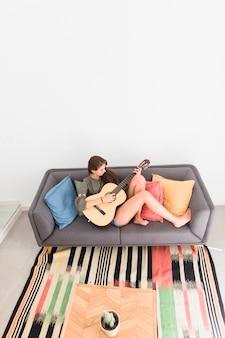 Erhöhte ansicht der entspannten jugendlichen, die auf dem sofa spielt gitarre sitzt