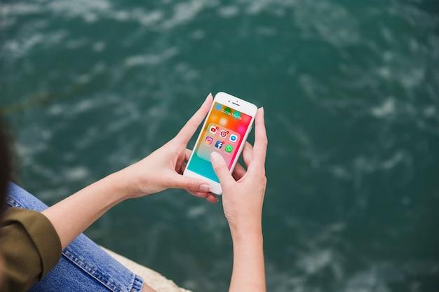 Erhöhte ansicht der frau, die mobiltelefon mit social media-mitteilungen auf schirm verwendet
