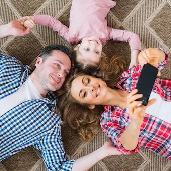 Erhöhte ansicht der frau, die selfie mit mann nimmt; und tochter im handy beim liegen auf teppich