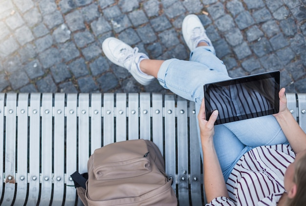 Erhöhte ansicht der frau sitzend auf der bank, die digitale tablette hält