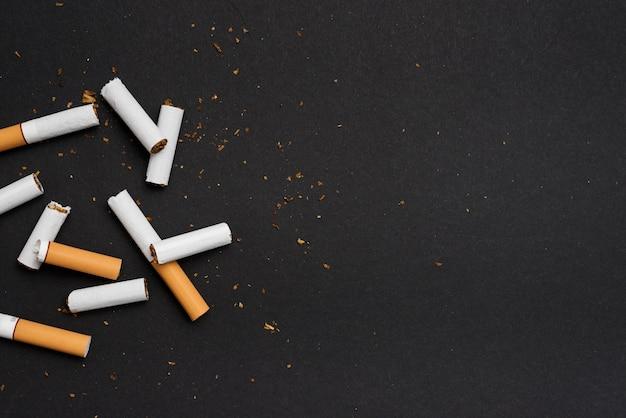 Erhöhte ansicht der gebrochenen zigarette über schwarzem hintergrund