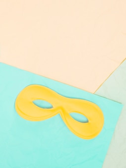 Erhöhte ansicht der gelben augenmaske über farbigem hintergrund