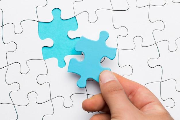 Erhöhte ansicht der hand blaues puzzlespielstück über weißem puzzlespielhintergrund halten