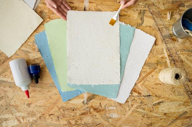 Erhöhte ansicht der hand einer frau unter verwendung des malerpinsels über handgemachten papieren