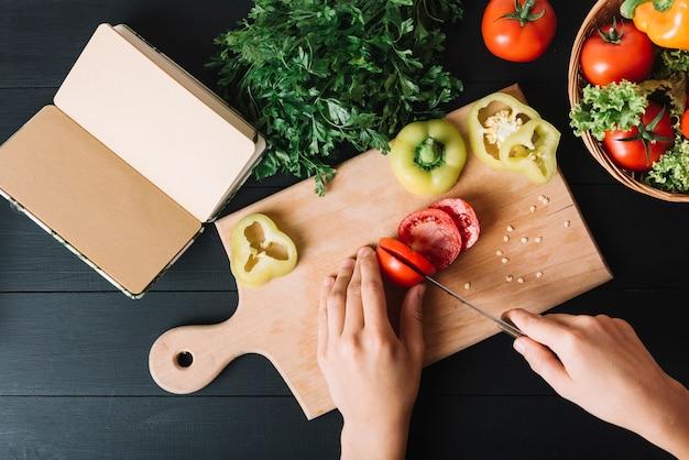 Erhöhte ansicht der hand einer person, die rote tomate auf hackendem brett schneidet